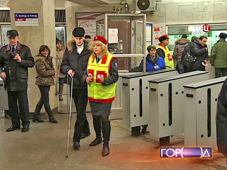 Сотрудник метрополитена помогает слабовидящему