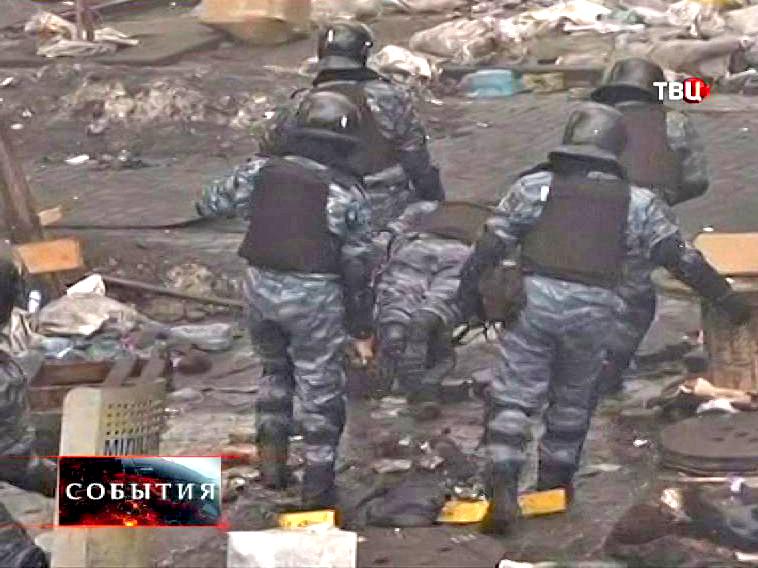 Милиционеры выносят раненного сотрудника во время беспорядка в Киеве