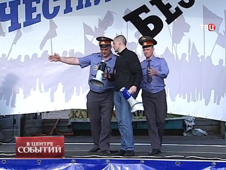 Представители полиции уводят Сергея Удальцова со сцены