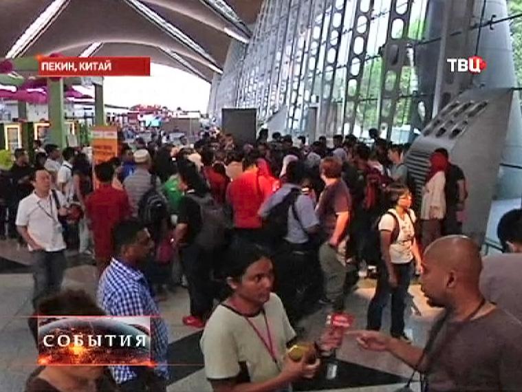 Люди в зале ожидания аэропорта Пекина