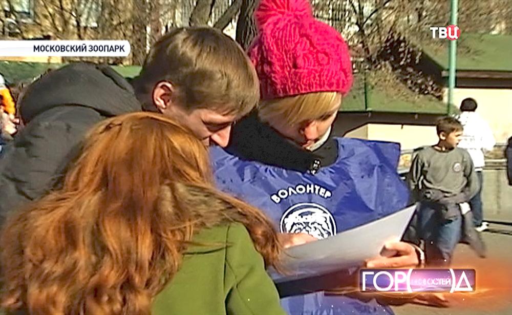 Волонтер показывает дорогу посетителям на карте