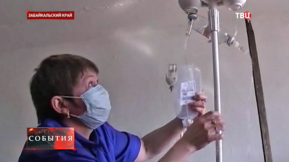Врачь в больнице в Забайкальском крае ставит капельницу пострадавшему от отравления алкоголем