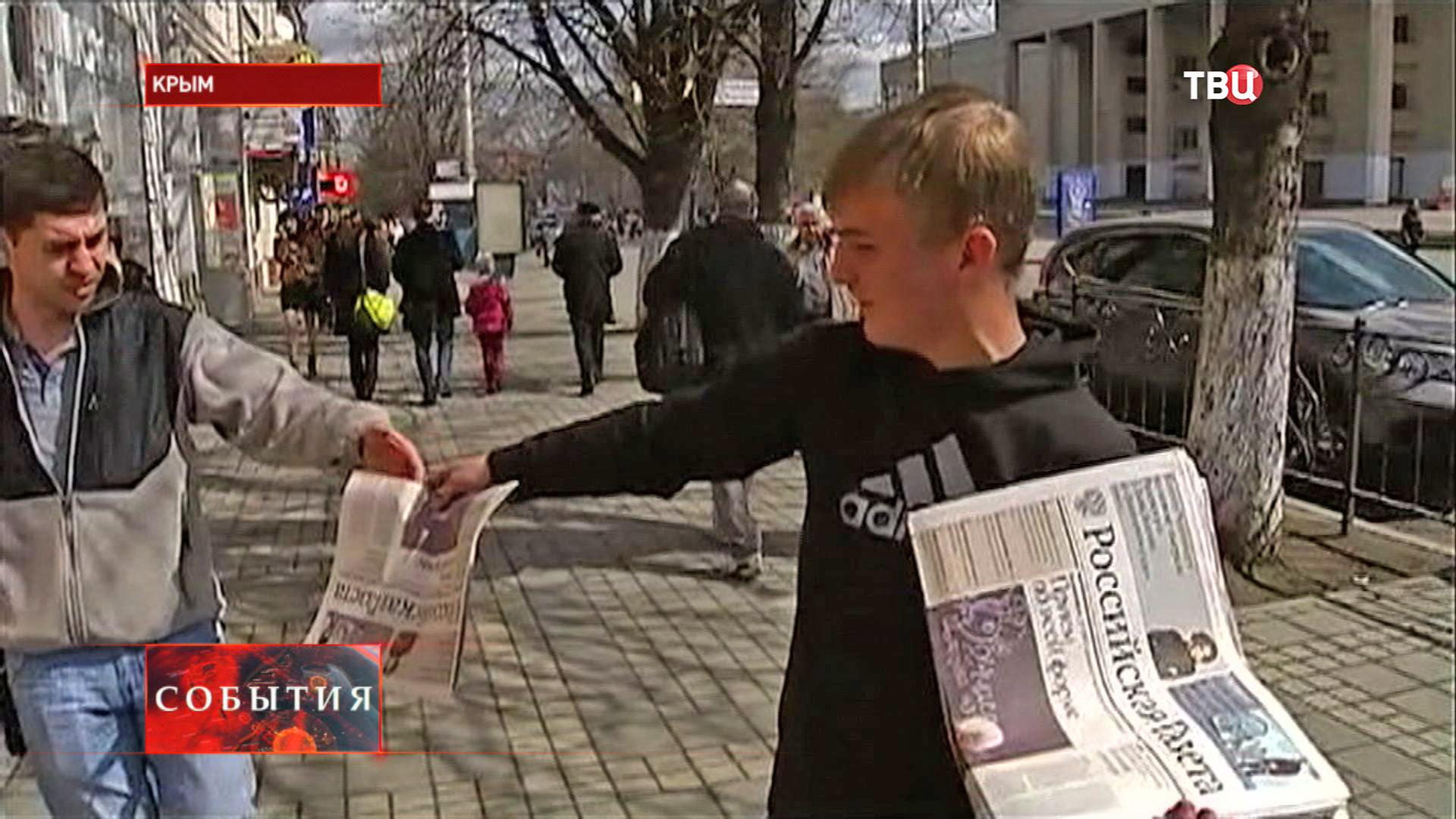 Молодой человек раздает прессу на улице Крыма
