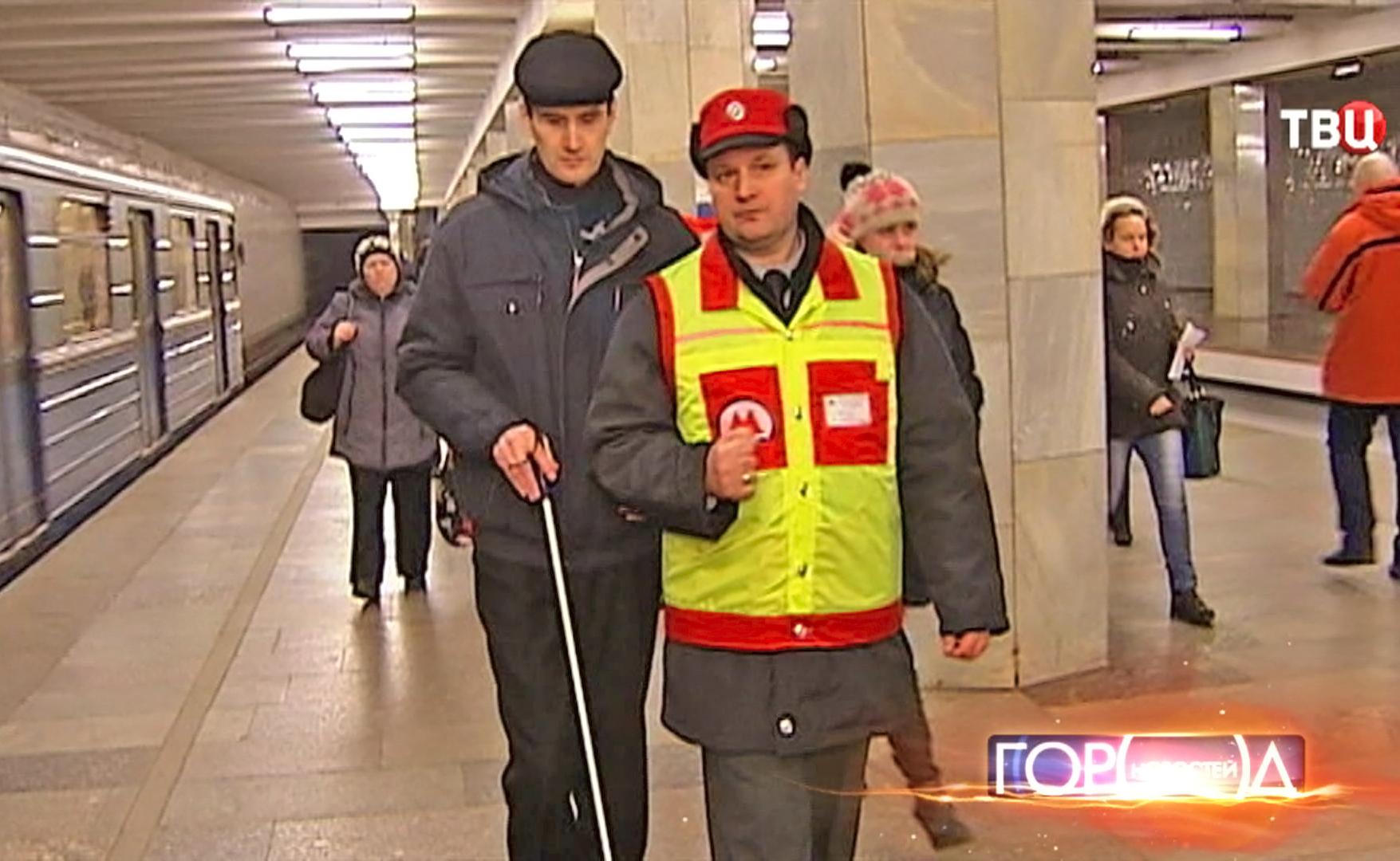 Инспектор помогает слабовидящему человеку передвигаться по метро