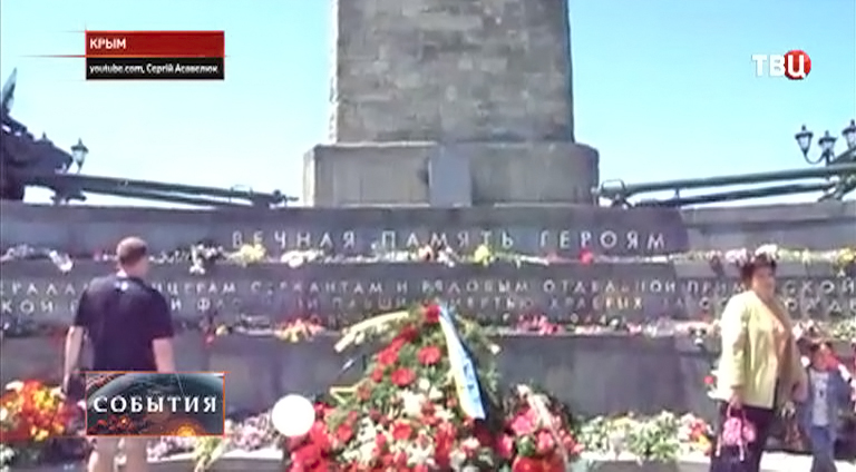 Люди несут цветы к мемориальной доске