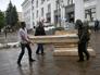 Местные жители складируют гробы и готовятся к приему тел погибших ополченцев