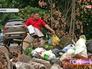 Мужчина выбрасывает мусор на обочину дороги