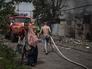Местные жители у разрушенного дома в поселке Луганская
