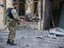Народный ополченец у жилого многоэтажного дома, поврежденного в результате артобстрела украинскими военными