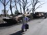 Местные жители у украинской военной техники, сгоревшей в результате боевых действий