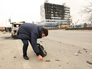 Сотрудник криминальной полиции собирает гильзы рядом со зданием Дома печати