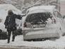 Женщина чистит от снега автомобиль во время снегопада во Владивостоке