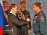 Дмитрий Медведев вручает награду сотруднику МЧС