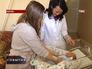Мама показывает новорожденного врачу