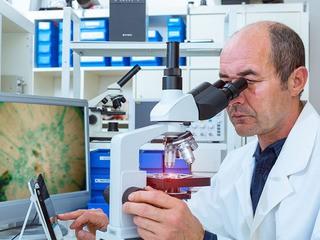 Учёный исследует при помощи микроскопа образцы биопсии