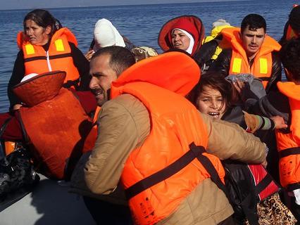 Мигранты сходят с лодки в Греции