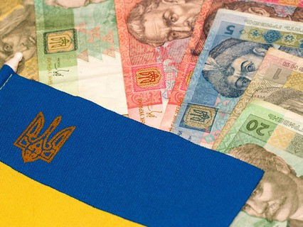 Украинские деньги на фоне национального флага