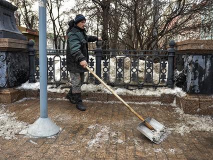 Рабочий убирает лёд с тротуара на Рождественском бульваре в Москве