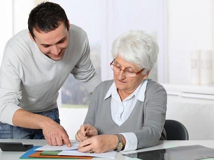 Пожилая женщина подписывает договор
