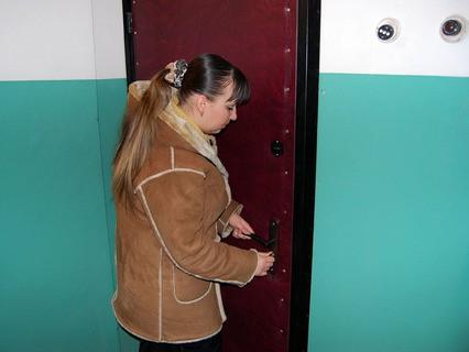 Девушка открывает дверь новой квартиры