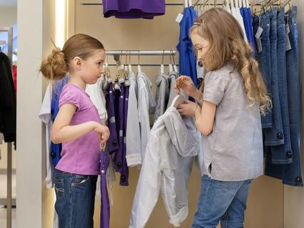 Девочки выбирают новые вещи в магазине детской одежды