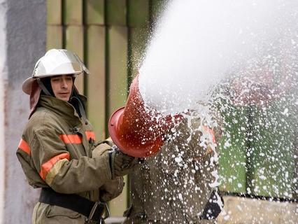 Пожарный льёт пену из шланга