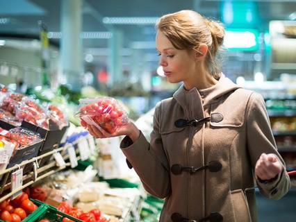 Девушка выбирает помидоры в супермаркете