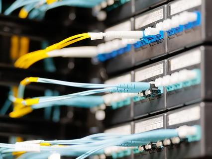 Оптические кабели, подключённые к панели в серверной комнате