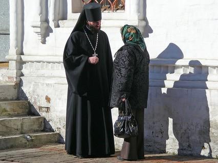 Священник разговаривает с прихожанкой