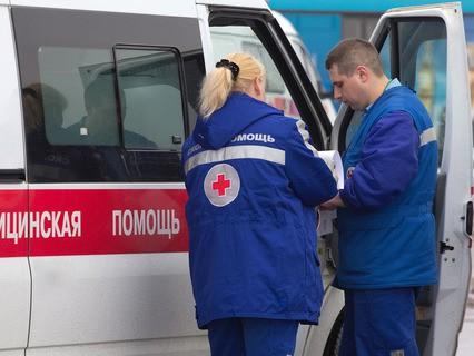 Бригада врачей у машины скорой медицинской помощи