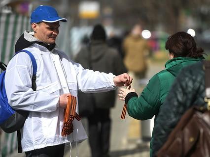 Волонтёр раздаёт георгиевские ленточки на Зубовском бульваре