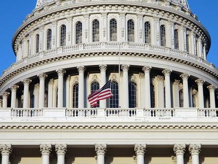 Здание Капитолия с развевающимся американским флагом. США