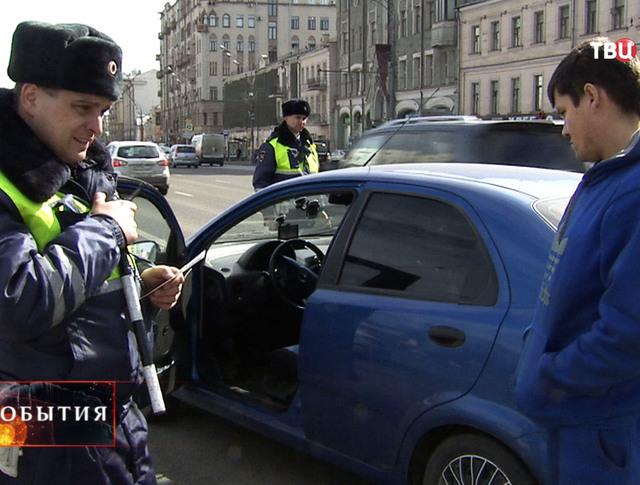Инспектор ДПС проверяет документы у автолюбителя