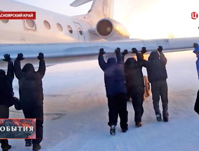 Пассажиры толкают примёрзший к ВПП Ту-134