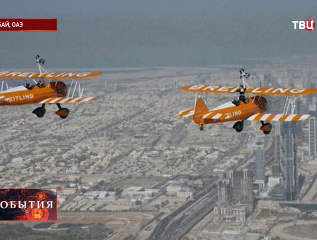 Воздушное шоу на крыльях бипланов в небе над Дубаем