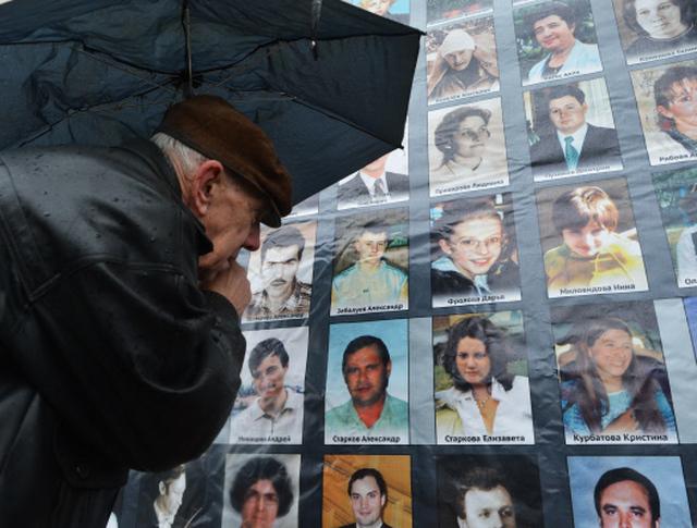Мужчина у стены с фотографиями в день памяти погибших в результате теракта на Дубровке