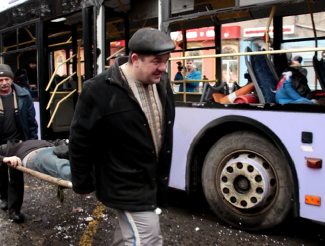 Жители Донецка выносят из троллейбуса пострадавшего в результате обстрела на остановке общественного транспорта