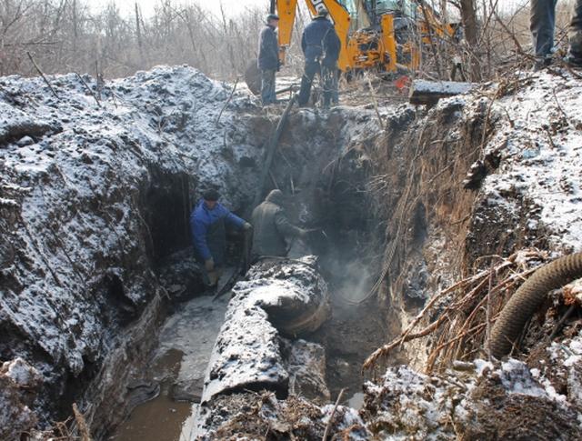 Рабочие у поврежденного трубопровода в Донецке