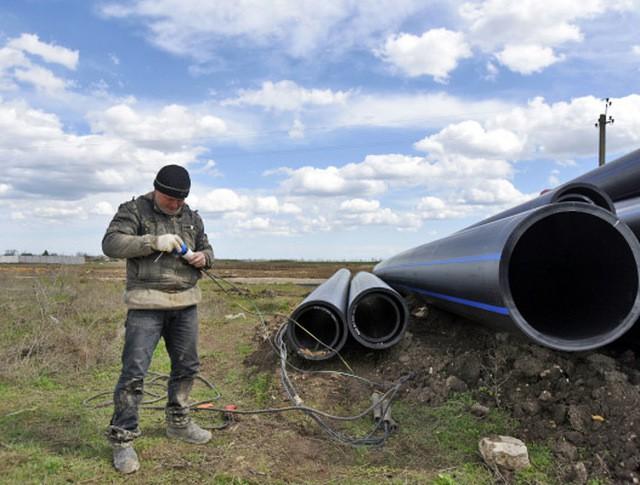 Рабочий выполняет работы по прокладке трубопровода к Северо-Крымскому каналу