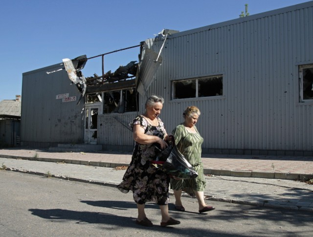 Прохожие у здания, пострадавшего в результате обстрела поселка Октябрьский в Куйбышевском районе города Донецка