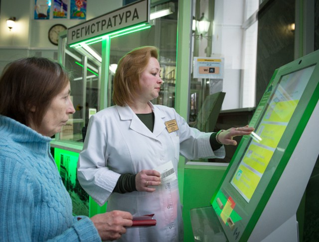 Сотрудница городской поликлиники помогает пациентке оформить талон на прием к врачу в терминале электронной очереди