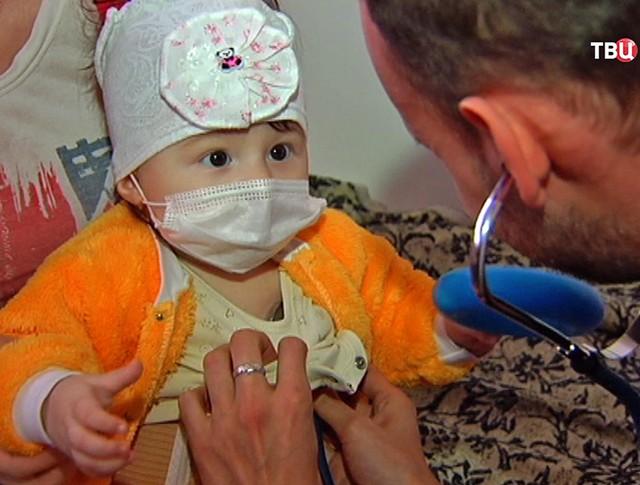 Врач осматривает девочку из Донецка