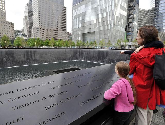Люди у мемориала и музея в Нью-Йорк на месте теракта 11 сентября
