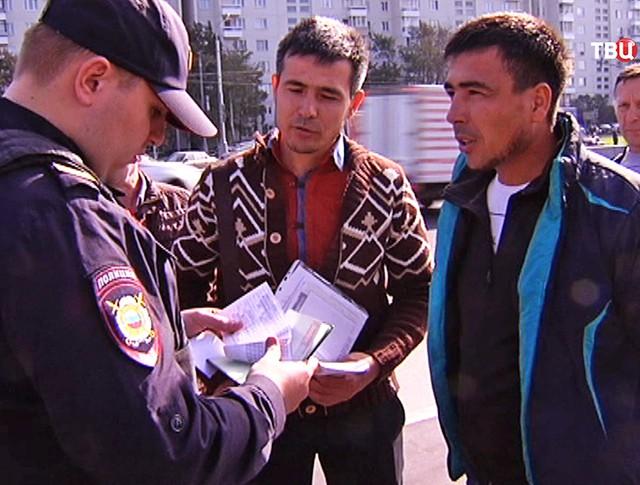 Полицейский проверяет документы у мигрантов
