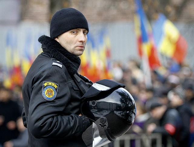 Сотрудник полиции во время акции протеста в Кишиневе, Молдавия