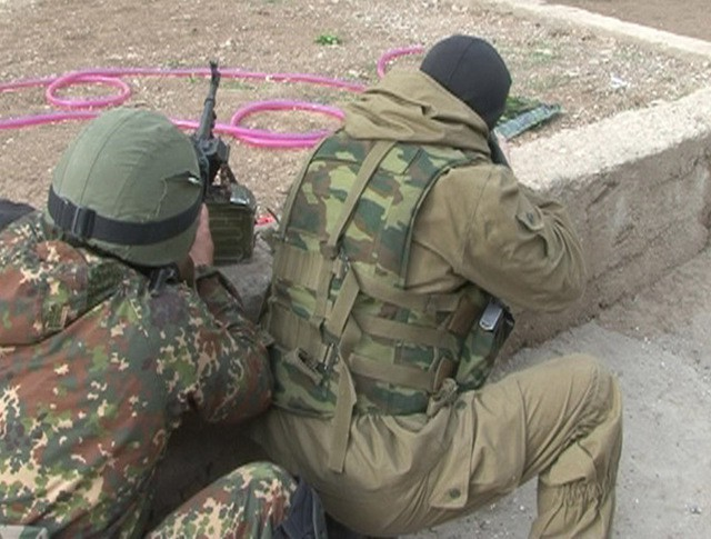 Бойцы спецназа ФСБ РФ ведут спецоперацию по ликвидации скрывающихся в одном из домов боевиков