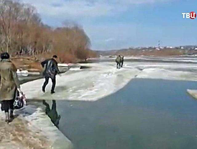 Жители переходят реку по льду