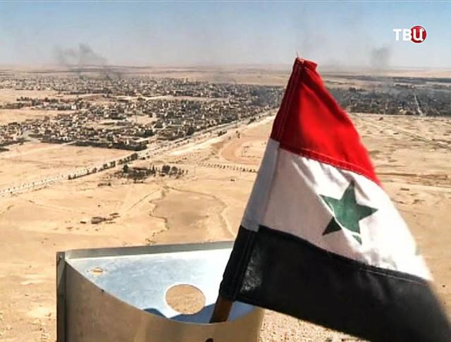 Флаг Сирии на фоне города