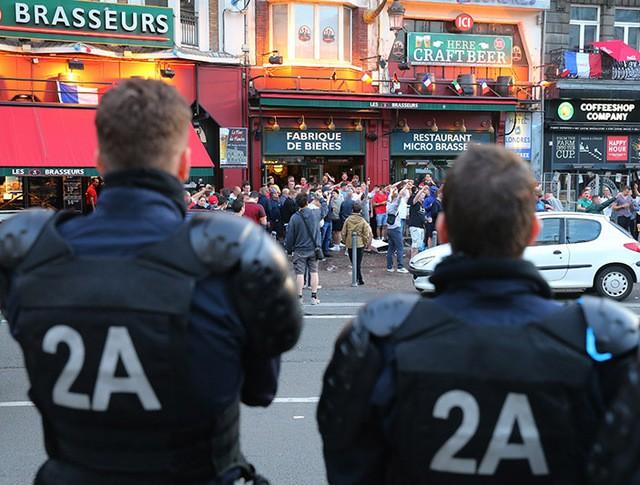 Сотрудники полиции наблюдают за болельщиками у бара на одной из улиц во французском городе Лилле