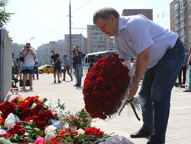 Люди несут цветы и свечи к посольству Франции